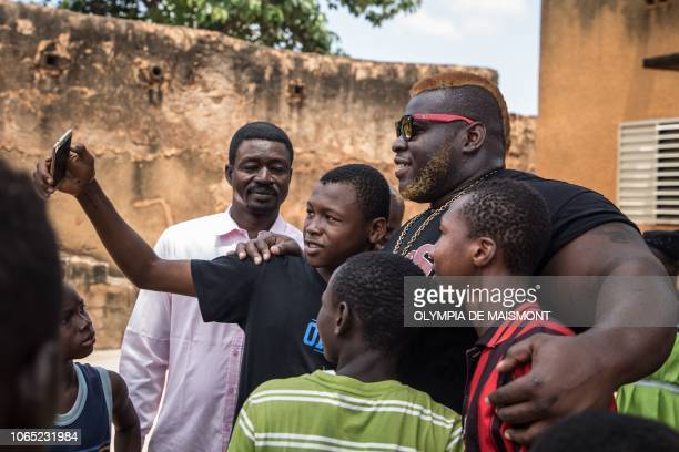 Cheick Ahmed AlHassan Sanou aka Iron Biby poses for pictures with young fans in his home town of BoboDioulasso second biggest city of Burkina Faso on...