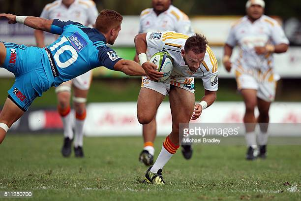 Cheifs Aaron Cruden steps past Blues Ihaia West during the Super Rugby preseason match between the Blues and the Chiefs at Pukekohe Stadium on...