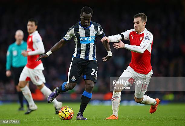 Cheik Ismael Tiote of Newcastle United and Aaron Ramsey of Arsenal compete for the ball during the Barclays Premier League match between Arsenal and...