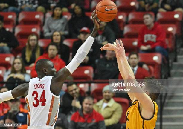 Cheikh Mbacke Diong of the UNLV Rebels blocks a shot from Hunter Thompson of the Wyoming Cowboys during their game at the Thomas Mack Center on...