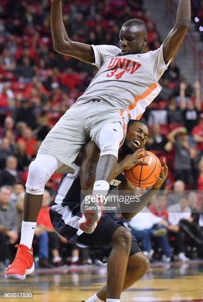 Cheikh Mbacke Diong of the UNLV Rebels lands on DeAngelo Isby of the Utah State Aggies during their game at the Thomas Mack Center on January 6 2018...