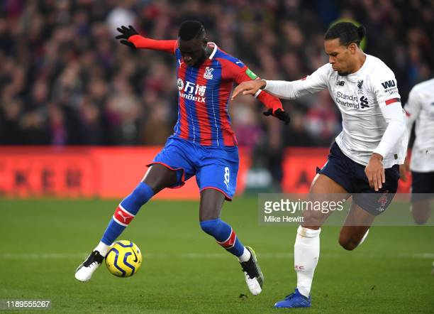 Cheikhou Kouyate of Crystal Palace battles for possession with Virgil van Dijk of Liverpool during the Premier League match between Crystal Palace...