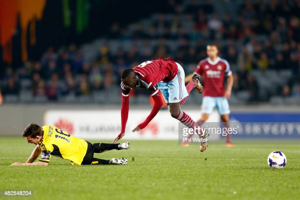 Cheikhou Kouyate of West Ham trips over Louis Fenton of the Phoenix during the Football United New Zealand Tour match between the Wellington Phoenix...