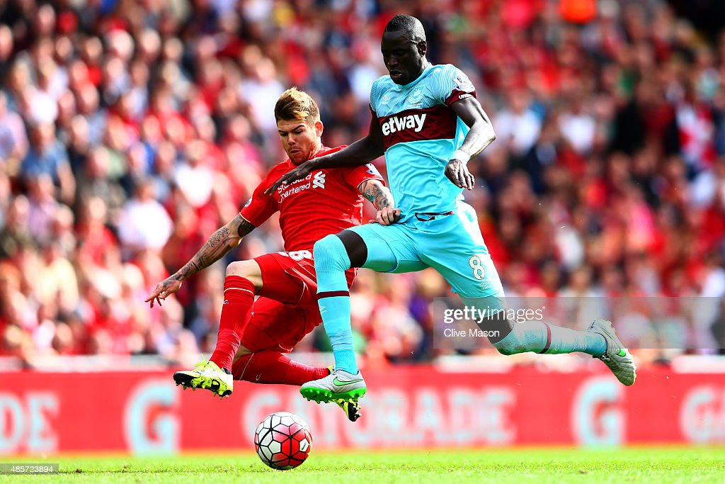 Cheikhou Kouyate of West Ham United and Alberto Moreno of Liverpool compete for the ball during the Barclays Premier League match between Liverpool and West Ham United at Anfield on August 29, 2015 in Liverpool, England.
