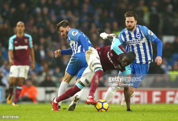 Cheikhou Kouyate of West Ham United is tackled by Pascal Gross of Brighton and Hove Albion and Davy Propper of Brighton and Hove Albion during the...