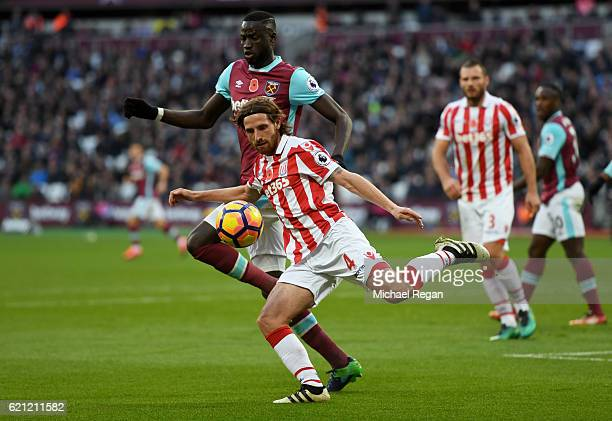Cheikhou Kouyate of West Ham United puts pressure on Joe Allen of Stoke City C during the Premier League match between West Ham United and Stoke City...