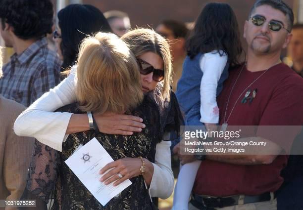 11/19/05 Chela Ortiz the wife of slain LA County Sheriff Deputy Jerry Ortiz hugs Emma Powell before the start of a service to dedicate a plaque in...