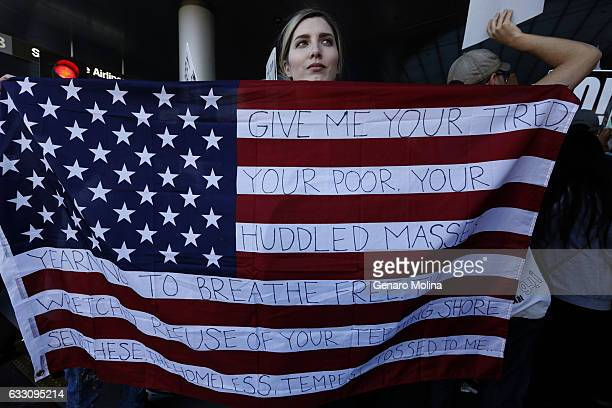 Chella from Sherman Oaks holds the US flag with words from the sonnet The New Colossus by poet Emma Lazarus while joining people who continue to...