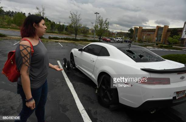 Chelsa Nava checks out the damage to her husbands car in the parking lot of the Colorado Mills Mall on May 8 2017 in Golden Colorado A hail storm...