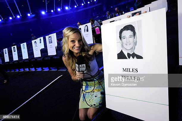 Chelsea Briggs from HollyWire TV poses with actor Miles Teller's place card during MTV Movie Awards press junket April 9 in Los Angeles California