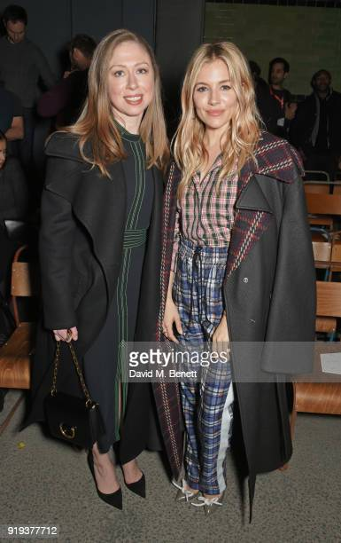 Chelsea Clinton and Sienna Miller wearing Burberry at the Burberry February 2018 show during London Fashion Week at Dimco Buildings on February 17...