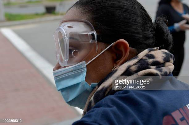 Chelsea Collaborative Inc volunteer Jessica Armijo wearing eye protection and a surgical mask helps distribute packages of donated food and goods to...