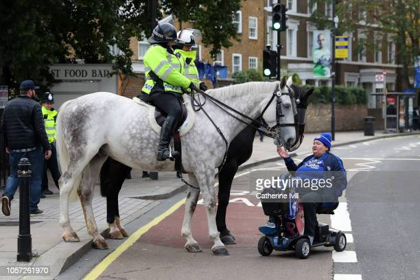 Chelsea fan is seen with Police horses prior to the Premier League match between Chelsea FC and Crystal Palace at Stamford Bridge on November 4 2018...