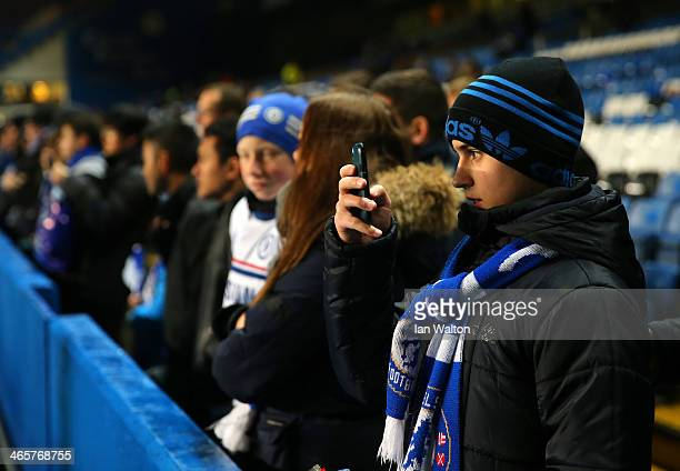 Chelsea fan take a photo on his smart phone ahead of the Barclays Premier League match between Chelsea and West Ham United at Stamford Bridge on...