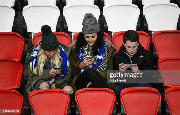Chelsea fans looks at their mobile phones prior to the UEFA Champions League round of 16 first leg match between Paris SaintGermain and Chelsea at...