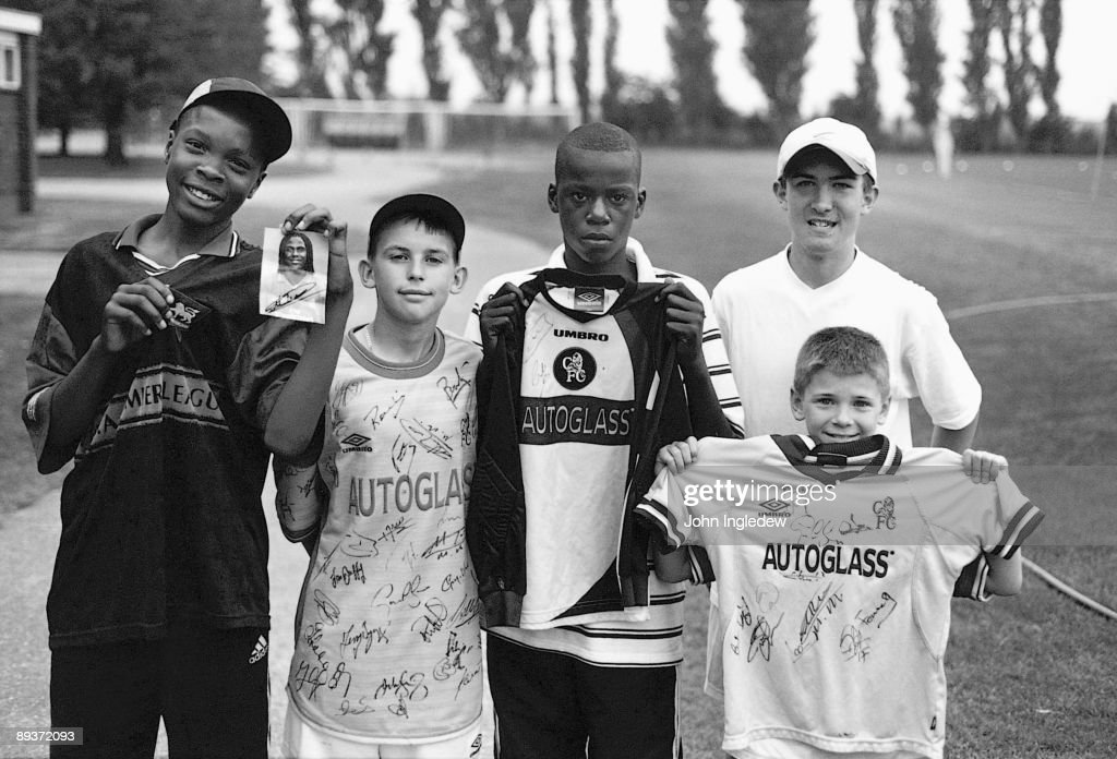 Chelsea fans pose with their autographs they picked up during a training session during the 2002/03 season at the Harlington training ground, in London.