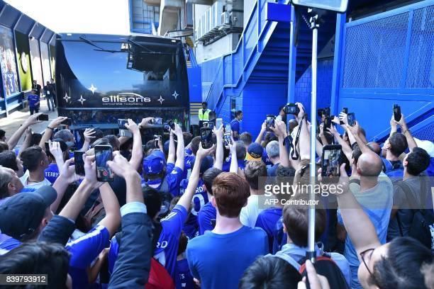 Chelsea fans take photographs and video of their players arriving at the ground ahead of the English Premier League football match between Chelsea...