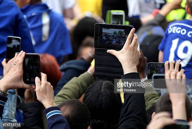 Chelsea fans take pictures on their phones duing the Chelsea FC Premier League Victory Parade on May 25 2015 in London England