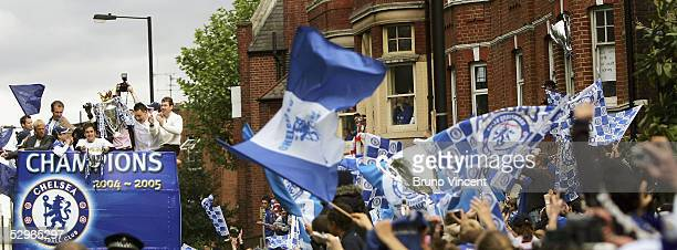 Chelsea fans wave flags as the team bus carrying the FA Barclays Premier League trophy and League Cup on the Chelsea Football Club victory parade on...