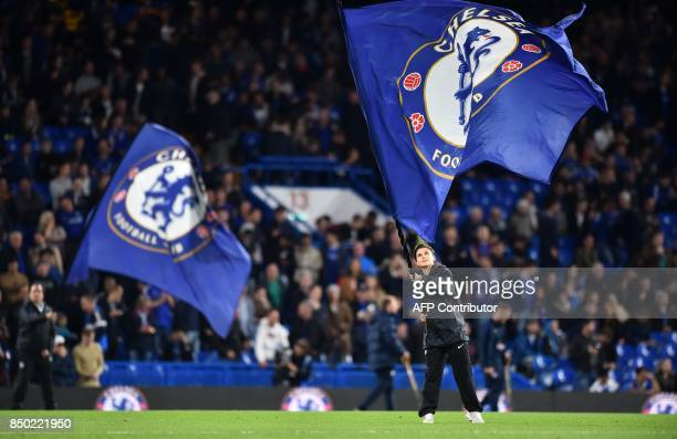 Chelsea flags are waved on the pitch ahead of the English League Cup third round football match between Chelsea and Nottingham Forest at Stamford...