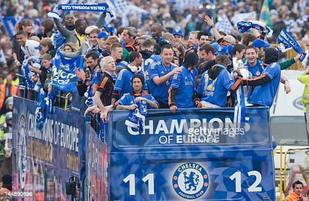 Chelsea Football Club players hold the Champions League and FA Cup as they ride on an opentop bus parade along Kings Road in west London on May 20...