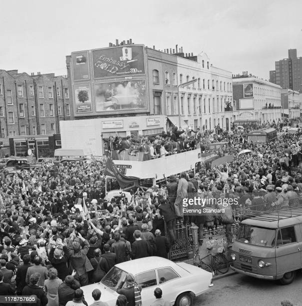 Chelsea Football Club team players standing on the top deck of an open top bus as they parade with the FA Cup trophy through the streets of Chelsea...