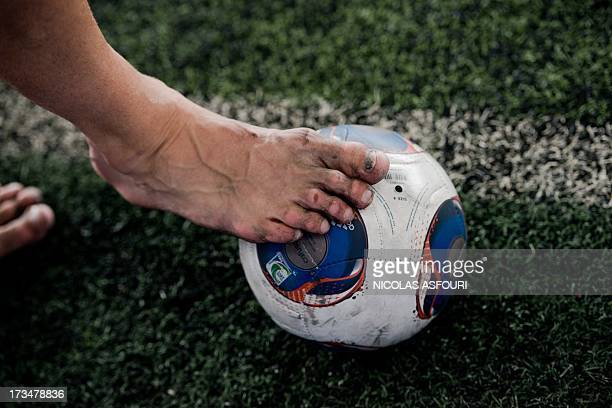 Chelsea football player Gary Cahill play sfootball bare feet during an exhibition training with Thai children at the super kick stadium in Bangkok on...