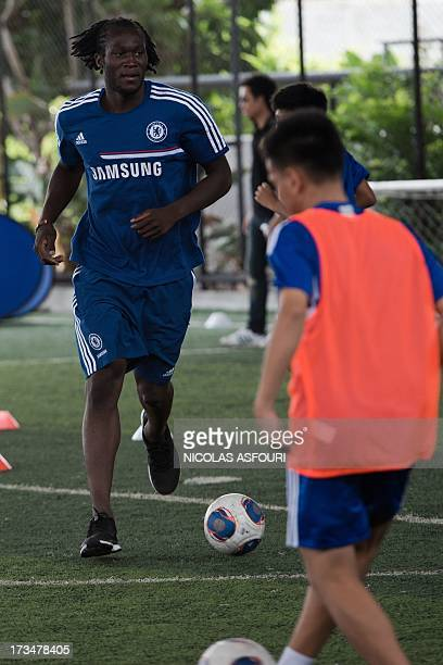 Chelsea football player Romelu Lukaku plays with the ball during an exhibition training with Thai children at the super kick stadium in Bangkok on...