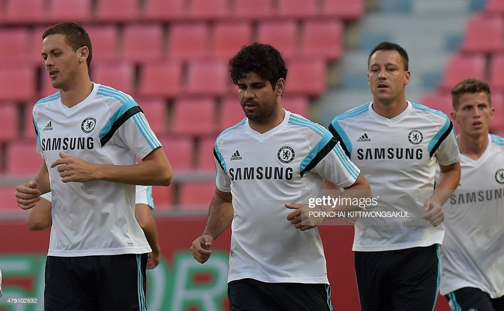 Chelsea football players Nemanja Matic (L), Diego Costa (C) John Terry (R) warm up during a team football training session at Rajamangala Stadium in Bangkok on May 29, 2015. The Blues will meet Thailand's All Stars at the 49,000-capacity Rajamangala Stadium in Bangkok for a special match on May 30. AFP PHOTO / Pornchai KITTIWONGSAKUL