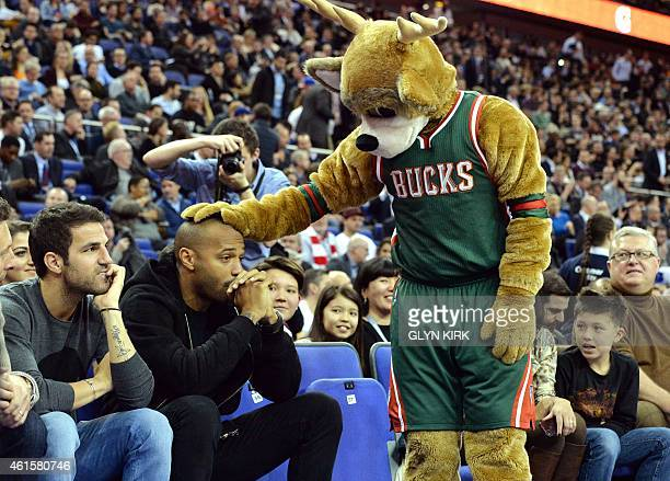 Chelsea footballer Cesc Fabregas looks on as former footballer Thierry Henry is bumped on the head by a Milwaukee Bucks team mascot during the 2015...