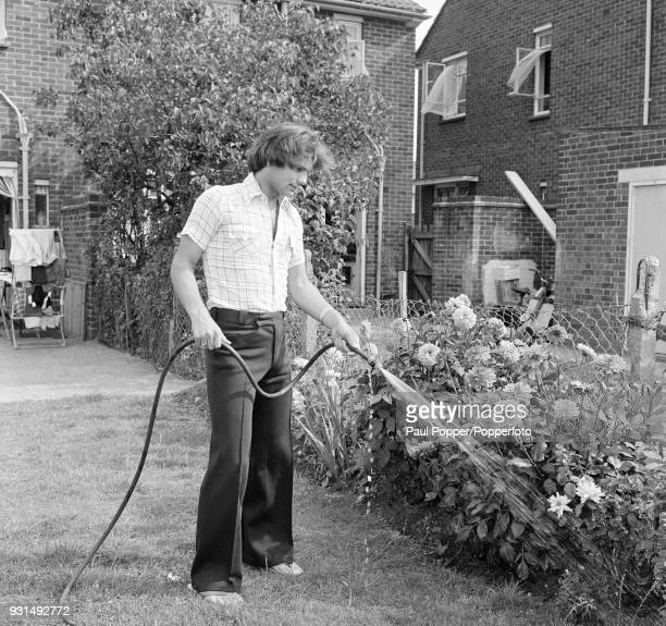 Chelsea footballer Ray Wilkins watering the garden at his mother's home in London circa August 1975