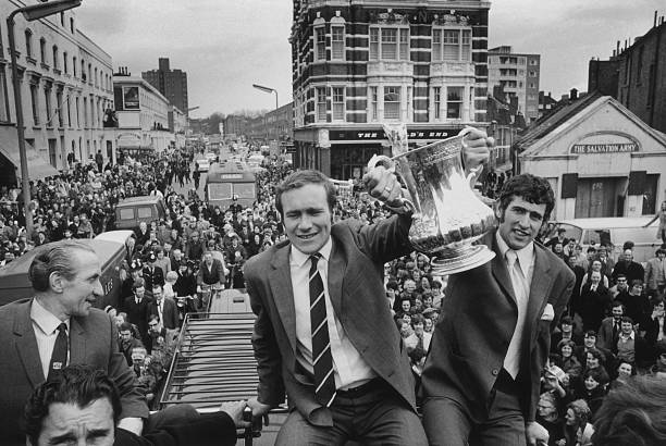 Chelsea footballers Ron Harris and Peter Bonetti lift the FA Cup during the team's open-top bus parade in front of their supporters, after Chelsea's...
