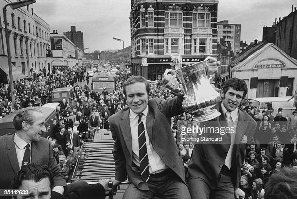Chelsea footballers Ron Harris and Peter Bonetti lift the FA Cup during the team's opentop bus parade in front of their supporters after Chelsea's 21...
