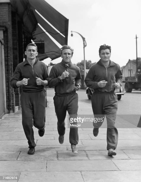 Chelsea footballers Roy Bentley Eric Parsons and Kenneth Armstrong on a training run in Chelsea High Street London 24th July 1952