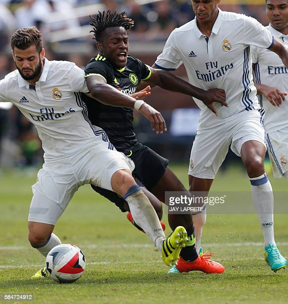 Chelsea forward Michy Batshuayi tries to pass the ball between Real Madrid defender Jose I Fernandez Iglesias and defender Raphael Varane during an...