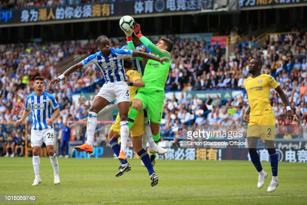 Chelsea goalkeeper Kepa Arrizabalaga catches the ball above Terence Kongolo of Huddersfield during the Premier League match between Huddersfield Town...