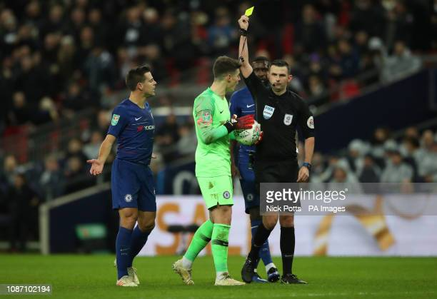 Chelsea goalkeeper Kepa Arrizabalaga is booked by referee Michael Oliver after foul on Tottenham Hotspur's Harry Kane who earned a penalty during the...
