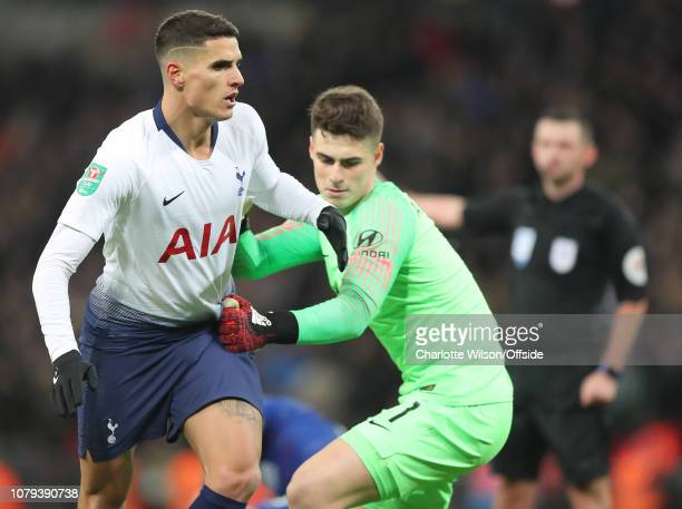 Chelsea goalkeeper Kepa Arrizabalaga pulls on the shirt and shorts of Erik Lamela of Tottenham as Lamela keeps playing after the whistle during the...
