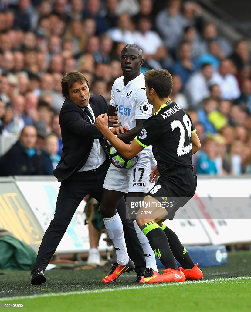 Chelsea manager Antonio Conte battles to get the ball back with Cesar Apilicueta (r) from Swansea forward Modou Barrow during the Premier League match between Swansea City and Chelsea at Liberty Stadium on September 11, 2016 in Swansea, Wales.