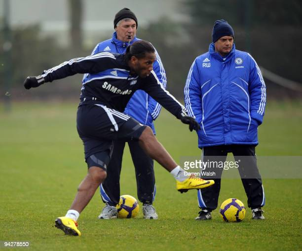 Chelsea manager Carlo Ancelotti and Ray Wilkins watch Didier Drogba during a training session at the Cobham training ground on December 11 2009 in...