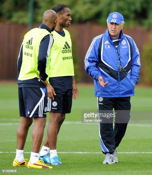 Chelsea manager Carlo Ancelotti talks to Didier Drogba and Nicolas Anelka during a training session the Cobham training ground on October 2 2009 in...