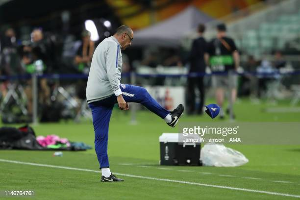 Chelsea manager head coach Maurizio Sarri walks off the pitch kicking his chelsea hat after an arguement during the Chelsea training session prior to...