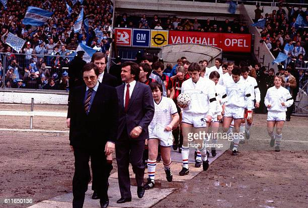 Chelsea Manager John Hollins and Manchetsr City Manager Billy McNeill lead out the teams