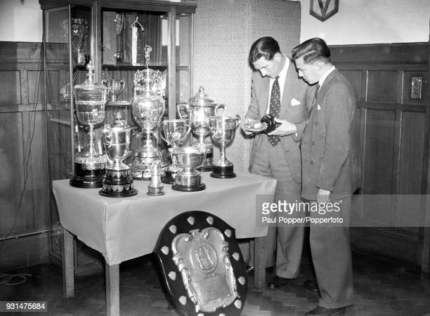 Chelsea manager Ted Drake with the club's programme editor Albert Sewell looking at trophies in the boardroom at Stamford Bridge in London 21st June...