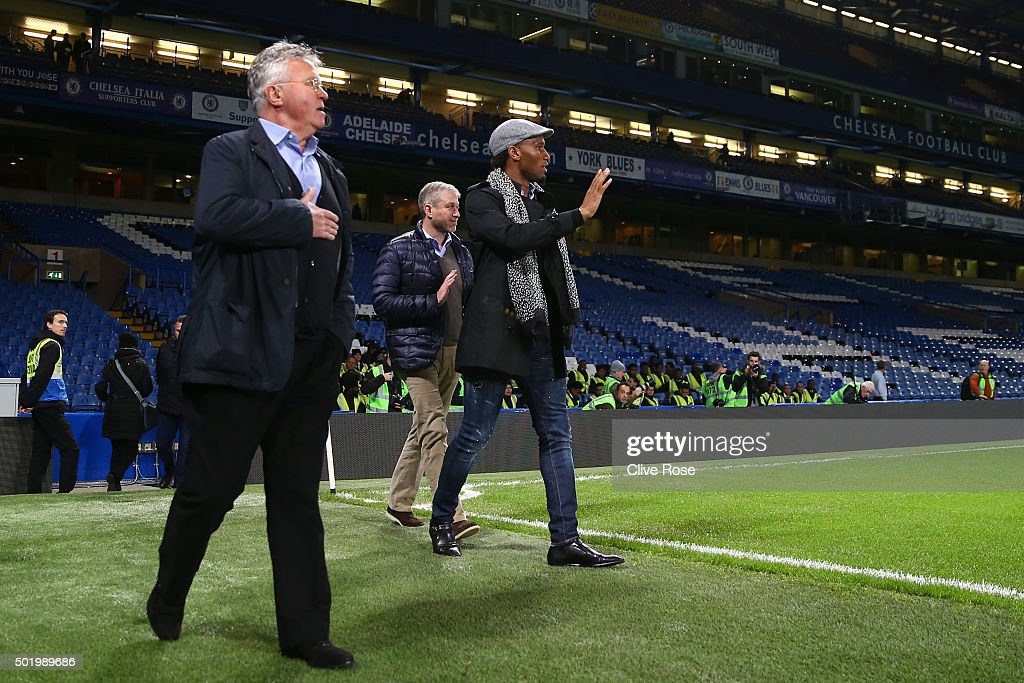 Chelsea owner Roman Abramovich (C), Chelsea interim manager Guus Hiddink (L) and Didier Drogba (R) walk into the pitch to congratulate players and staffs including Gary Cahill (1st L) and Loic Remy (2nd L) after their 3-1 win in the Barclays Premier League match between Chelsea and Sunderland at Stamford Bridge on December 19, 2015 in London, England.