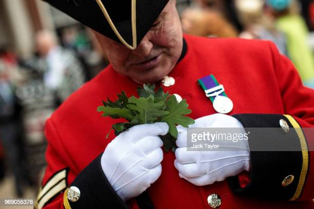Chelsea Pensioner attaches oak leaves to his uniform ahead of the Founder's Day Parade at Royal Hospital Chelsea on June 7 2018 in London England The...
