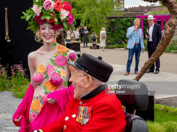Chelsea Pensioner George observes a woman with flowers painted on her body on press day at Chelsea Flower Show on May 20 2019 in London England The...