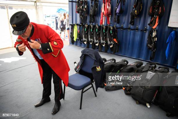 Chelsea pensioner Mike Smith puts on his traditional scarlet coat ahead of his 100th skydive at the Old Sarum airfield on August 10 2017 in Salisbury...
