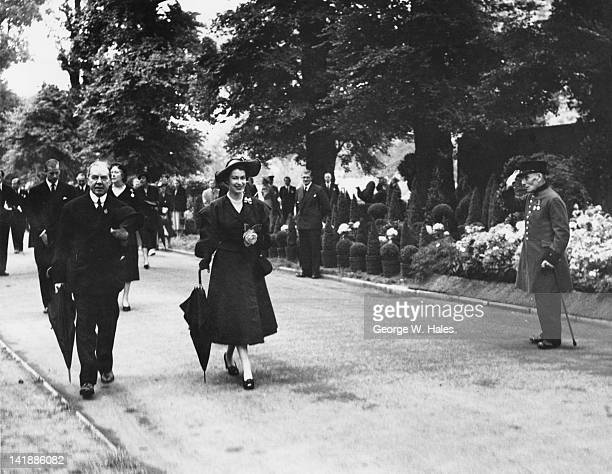 A Chelsea pensioner salutes Queen Elizabeth II as she tours the Chelsea Flower Show London 20th May 1952 The Queen is accompanied by Henry McLaren...