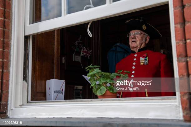 Chelsea Pensioner sings as he watches a Remembrance Day service from his window at Royal Hospital Chelsea on November 8, 2020 in London, England. The...